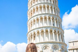 Little girl on italian vacation near the famous Leaning Tower of Pisa, Italy