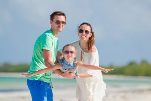 Happy family of three having fun together on the beach