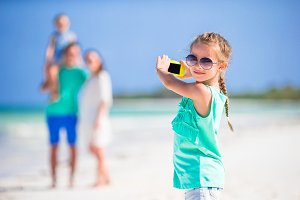 Little girl making photo on phone of family at the beach