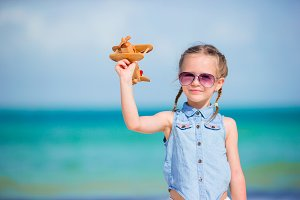 Happy little girl with toy airplane in hands on white sandy beach
