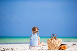 Adorable little girl with beach bag and towel during summer vacation