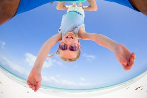 Little girl outdoors during summer vacation have fun with father. Portrait of a kid upside down on a sky background