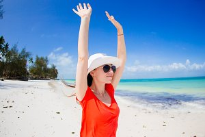 Happy woman in hat on tropical beach enjoy her vacation