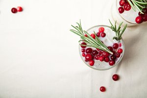 Coconut margarita with cranberries and rosemary