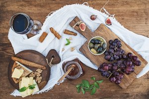 Glass of red wine, cheese board, grapes