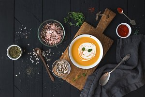 Pumpkin soup with cream, seeds and spices in rustic metal bowl