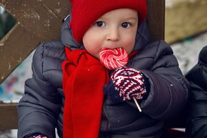 baby in red hat sits on a bench in the street with candy