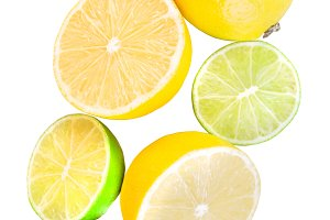 Slices and whole lemons and limes isolated on white background.