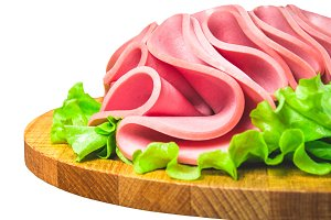 Breakfast luncheon Turkish sausage. Slices of beef meat in the form of mortadella on salad. Isolated on white background.