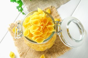Culinary background with conchiglie pasta on wooden table. Pasta in the form of cockleshells in a glass jar with parsley.