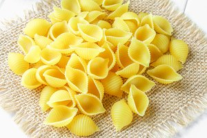Culinary background with conchiglie pasta on wooden table. Pasta in the form of seashells on a sack with parsley.