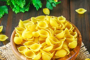 Culinary background with conchiglie pasta on wooden table. Pasta in the form of cockleshells in a wooden bowl with parsley.