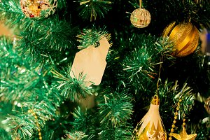 Christmas tree decorated with beautiful golden ornaments and empty card hanging - to insert any text