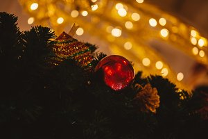 Beautiful decorated Christmas tree background with bauble and xmas ornaments blurred in gold bokeh