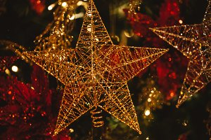 Close-up of golden Christmas detailed glittering star hanging on Christmas tree