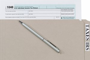 Tax form in folder with pen