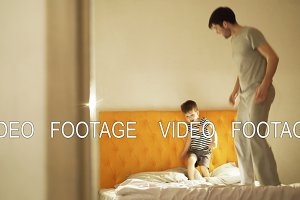 Happy father with little son dancing and have fun on bed at home in the evening before bedtime