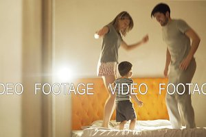 Happy family with little son dancing on bed at home in the evening before sleeping