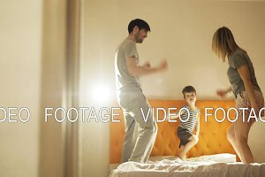 Happy family with little son dancing and have fun on bed at home in the evening before bedtime