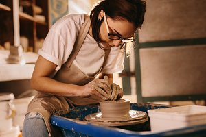 Female potter making a clay bowl