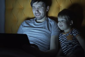 Young father and his little son watching cartoon movie using laptop computer while lying in bed in evening at home
