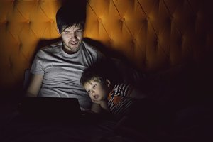 Young father and his little son watching cartoon movie using tablet computer and talking while lying in bed in evening at home