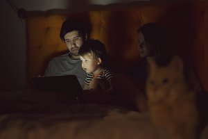 Happy family with little son learning to play tablet computer lying in bed with cat at home