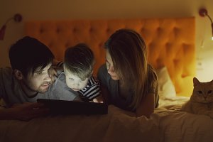 Happy family with little son and funny cat lying in bed at home and surfing social media on tablet computer before sleeping