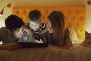 Happy family with little son and funny cat lying in bed at home and using tablet computer for playing game before sleeping