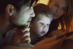 Closeup of Happy young family lying in bed at home while little boy learning to play digital tablet computer before sleeping time