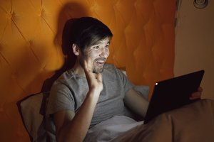 Young cheerful man using tablet computer having online video chat with girlfriend while lying in bed at home before sleeping
