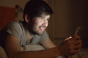 Closeup of Young smiling man using smartphone for surfing social media lying in bed at home at night