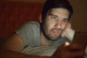 Close-up of young bored man having internet addiction and insomnia using smartphone lying in bed at home at night