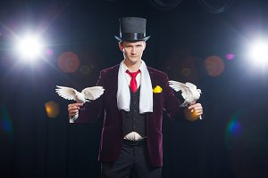 The magician with a two flying white Doves. on a black background