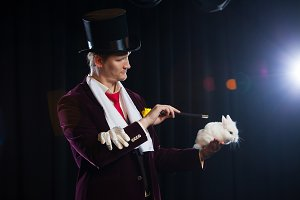 Magician with rabbit, Juggler man, Funny person, Black magic, Illusion on a black background