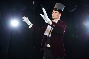 Magician with fly ball, Juggler man, Funny person, Black magic, Illusion A focus with a levitating cane with a magic wand on a black background