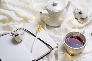 Warm knitted plaid,cup of hot tea and notebook