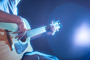 the hand of man playing acoustic guitar, close-up, flash of light, a beautiful light in the background