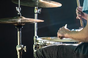 man plays the drum, flash of light, a beautiful light in the background with copy space