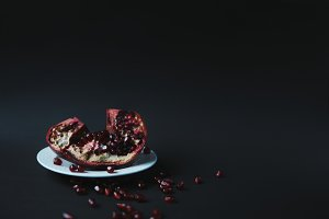 Pomegranate with grains on plate