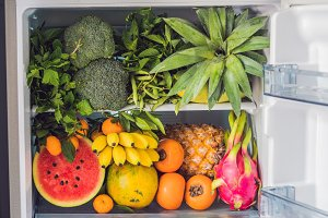 Opened refrigerator full of vegetarian healthy food, vibrant colour vegetables and fruits inside on fridge. Vegan Fridge