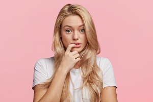 Beautiful female with puzzled expression, keeps finger on lips, listens interlocutor in bewilderment, poses against pink background. Studio shot of frustrated blonde woman with pure healthy skin