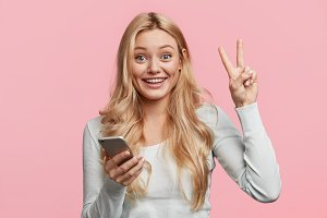 Portrait of pretty young female blogger being glad to update multimedia information on website. Positive woman enjoys free time with modern cellphone, gestures, isolated over pink background
