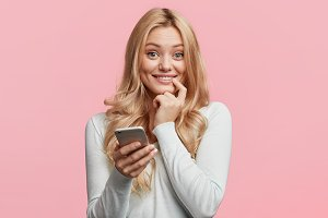 Smiling blonde female blogger uses smart phone for surfing her webpage, being satisfied with website popularity, has many feedbacks from followers, connected to wireless internet, isolated on pink