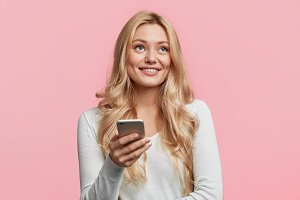 Cute dreamful smiling young beautiful female holds modern smart phone reads news on website, has joy as enjoys online communication with friends via social networks, isolated over pink background.