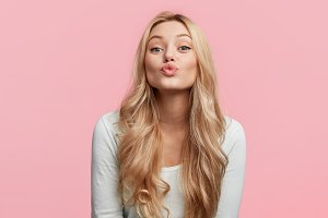 Isolated shot of beautiful female has long light hair, rounds lips, going to kiss someone, poses against pink background, has cheerful expression. Pretty woman expresses sympathy to handsome man