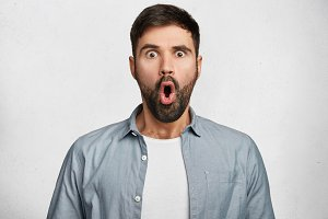 Stunned shocked young bearded male stares at camera with widely opened mouth, being surprised to see something awful or recieve bad news, poses against white background. Human attitude and reaction