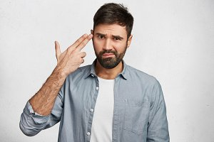 Stressed bearded male student being tired of session and preparing for exams, pretends kill himself, isolated over white background. Indoor shot of handsome guy demonstrates suicide gesture.