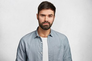 Portrait of serious bearded male wears fashionable denim shirt, hears attentively something important, isolated over white concrete wall. Young male student with thick beard and mustache indoor