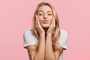 Portrait of lovely blonde female rounds lips as going to recieve kiss from boyfriend, looks at camera with pleased expression, isolated over pink background. Beautiful young woman poses in studio